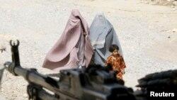 រូបឯកសារ៖ ស្ត្រីនិងកុមារីជនជាតិអាហ្វហ្គានីស្ថានដើរកាត់ប៉ុស្ដិ៍ប៉ូលិសក្នុងស្រុកមួយ នៅក្រុង Kandahar ប៉ែកខាងត្បូងប្រទេសអាហ្វហ្គានីស្ថាន ថ្ងៃទី២២ ខែមីនា ឆ្នាំ២០២១។