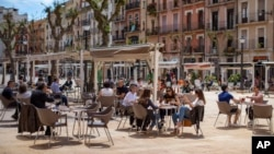 Ljudi sjede u bašti kafića u Taragoni, u Španiji (Foto: AP)