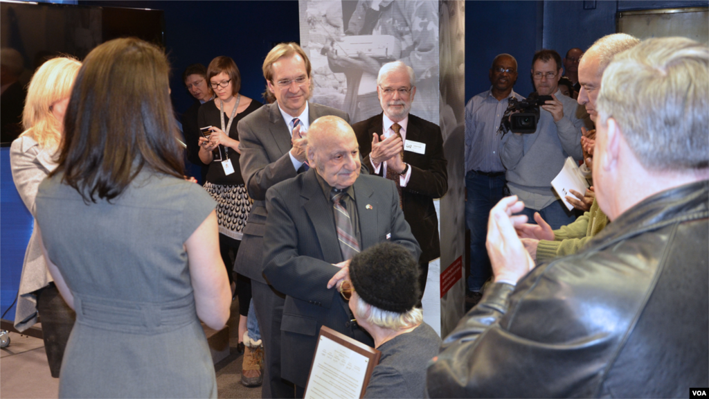 "VOA colleagues surround the ""Music Man"" following his speech at the studio dedication ceremony on January 23, 2014."