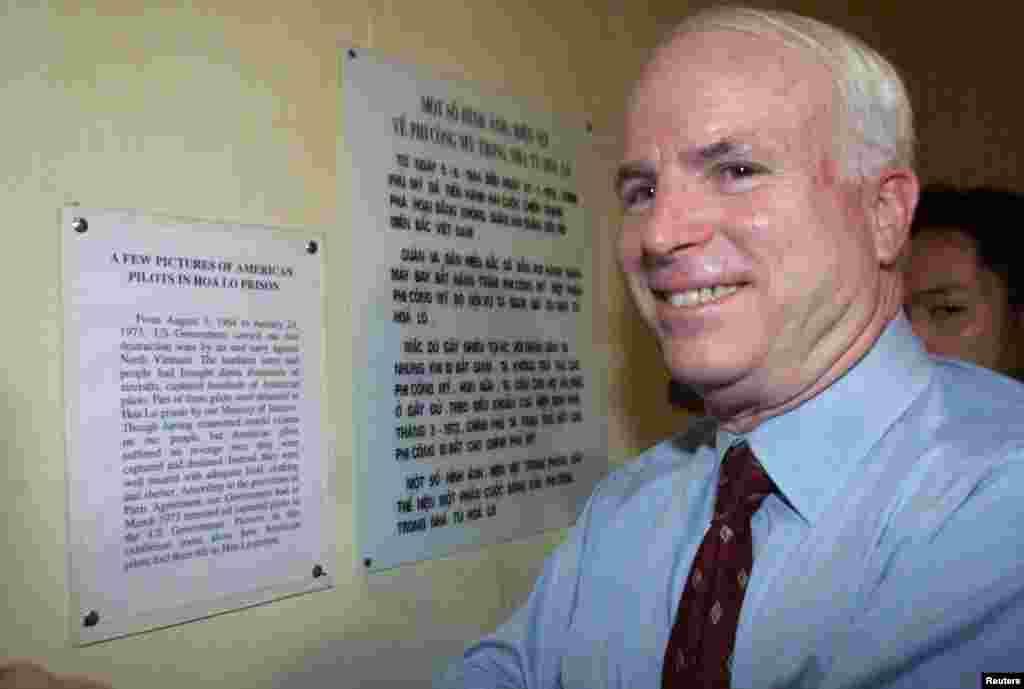 """Ông McCain mỉm cười gượng gạo trước bảng thông tin tuyên truyền của Việt Nam nói rằng tù nhân chiến tranh Mỹ được đối đãi tốt và không bị người Việt Nam trả thù, khi ông tham quan nhà tù Hỏa Lò vào ngày 26 tháng 4 năm 2000 tại Hà Nội. Sau khi đọc xong, ông McCain nói nó có tính """"giải trí tốt,"""" theo Reuters."""