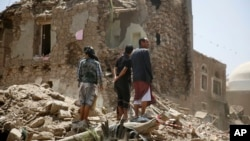 People stand amid the rubble of a house damaged by Saudi-led airstrike in the old city of Sana'a, Yemen, Sept. 19, 2015.