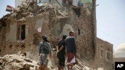 Orang-orang memperhatikan rumah yang rusak akibat serangan udara yang dipimpin Arab Saudi di kota tua Sana'a, Yaman, 19 September 2015.