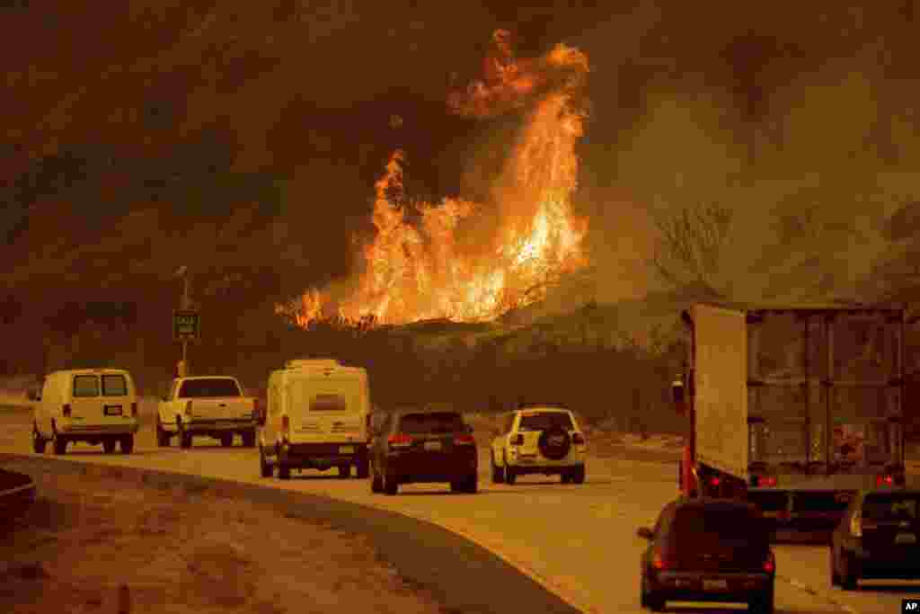 Flames from a wildfire leap above traffic on Highway 101 north of Ventura, California, Dec. 6, 2017.
