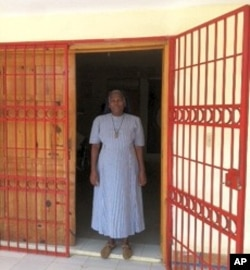 Sister Nellie stands in front of the hospital
