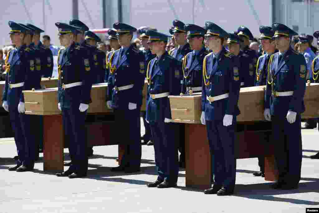 Honor guards take part in a ceremony for the victims of Malaysia Airlines MH17 before they are loaded on a transport plane heading to the Netherlands, at Kharkiv Airport, Ukraine, July 23, 2014.