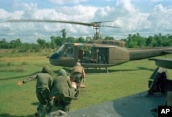 U.S. paratroopers carry a wounded man on a stretcher into a waiting helicopter in Vietnam, May 7, 1966.