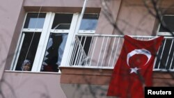 A woman looks through a damaged window in her home, close to the site of Wednesday's suicide bomb attack in Ankara, Turkey, Feb. 19, 2016.