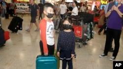 资料照:戴着口罩的儿童从武汉抵达悉尼机场。(2020年1月23日)