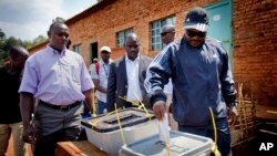 In this 2010 file photo, Burundian president Pierre Nkurunziza, right, casts his vote at a polling station in his hometown of Mumba in Ngozi province, northern Burundi. (AP Photo/Sylvain Liechti)