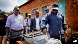 Burundian president Pierre Nkurunziza, right, casts his vote at a polling station in his hometown of Mumba in Ngozi province, northern Burundi.