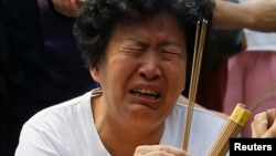 A family member of a passenger aboard the missing Malaysia Airlines flight MH370 cries as she burns incense to pray at Yonghegong Lama Temple in Beijing, June 15, 2014.