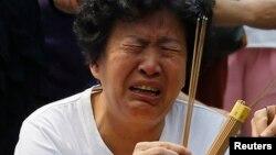 15일 중국 베이징 라마 사원에서 말레이시아 여객기 실종사고 탑승객 유가족이 분향하고 있다.