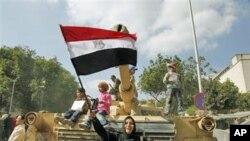 2月12日一名妇女在开罗解放广场一辆坦克前会晤埃及国旗欢庆胜利