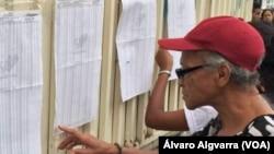 En la foto, ciudadanos revisan el listado de inscripción de documentos, en colegios electorales dispuestos para las elecciones regionales.