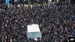 Ribuan warga Yahudi ultra-Ortodoks menghadiri prosesi pemakaman rabi terkemuka Meshulam Soloveitchik, di Yerusalem, mengabaikan aturan lockdown, Minggu, 31 Januari 2021.