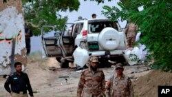 Los funcionarios de seguridad paquistaníes están de guardia en el sitio de un atentado suicida que mató a docenas de personas y dejó a muchos heridos en el distrito de Mastung cerca de Quetta, Pakistán, el viernes 12 de mayo de 2017.