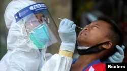 A medical worker performs a nose swab on a migrant boy at a seafood market, amid the coronavirus disease (COVID-19) outbreak, in Samut Sakhon province, in Thailand, December 19, 2020. REUTERS/Panumas Sa