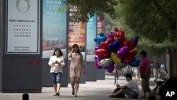 2013年6月26日,一位摊贩坐在北京街头人行道上贩卖气球。