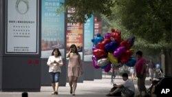 2013年6月26日,一位攤販坐在北京街頭人行道上販賣氣球。