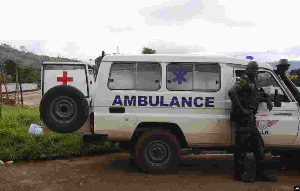 Un soldat Cameroun, à droite, se tient à côté d'une ambulance utilisée pour transporter les victimes du déraillement d'un train vendredi à Eseka, Cameroun, 22 octobre 2016.
