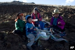 The Pacco family eats dinner after harvesting potatoes in Paru Paru, in the Cusco region of Peru, May 26, 2016.
