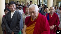 Newly elected PM Lobsang Sangay, left, and outgoing PM Samdhong Rinpoche, center, walk out of the prayer hall at the Tsuglakhang temple in Dharmsala, India, August 3, 2011