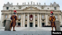 "FILE - Two Swiss Guards stand as Pope Francis waves as he delivers his first ""Urbi et Orbi"" message from the balcony overlooking St. Peter's Square at the Vatican, Dec. 25, 2013."