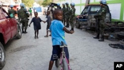 FILE - Children play in the street while United Nations peacekeepers from Brazil patrol in the Cite Soleil slum, in Port-au-Prince, Haiti, Feb. 22, 2017.