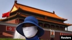 Женщина в маске на площади Тяньаньмэнь в центре Пекина, Китай