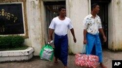 Dua tahanan politik Burma berjalan keluar dari penjara Insein di Yangon (Rangun), Burma, setelah mendapatkan amnesti dari Presiden Thein Sein, Selasa (23/7).