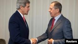 Državni sekretar Džon Keri i njegov ruski kolega Sergej Lavrov rukuju se pre današnjeg susreta u Ženevi