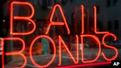 FILE - In this July 7, 2015, file photo, a sign advertising a bail bonds business is displayed near Brooklyn's jail and courthouse complex in New York.