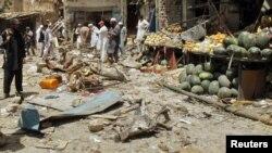 Petugas keamanan dan para pedagang berkumpul di sekitar lokasi ledakan bom di Landi Kotal, Pakistan (16/8). Ledakan bom yang dipasang di sebuah truk terbuka menewaskan 25 orang dan melukai sedikitnya 50 lainnya di desa ini.