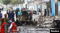 Security officers gather at the scene of a suicide car bombing at a street junction near the president's residence, in Mogadishu, Somalia, Sept. 25, 2021.