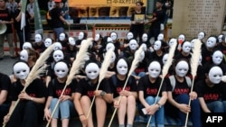 "Taiwanese NGO group members wear masks during a rally to demand that the Japanese government apologize to Taiwanese ""comfort women"" in Taipei on Aug. 14, 2018."