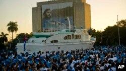 Estudiantes cubanos asisten al desfile militar del lunes 2 de enero en honor del desaparecido líder Fidel Castro, junto a una réplica del yate Granma en la Plaza de la Revolución de La Habana.