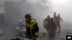 This frame grab from video released Feb 24, 2018, by the Syrian civil defense group known as the White Helmets shows members of the group helping residents during airstrikes and shelling by Syrian government forces, in Ghouta, a suburb of Damascus, Syria.