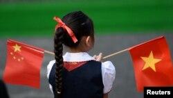 Một học sinh cầm lá cờ Việt Nam và Trung Quốc tại Phủ Thủ tướng ở Hà Nội hôm 12/11/2017. Công luận Việt Nam đang lo ngại về sự ảnh hưởng của Trung Quốc tới an ninh và chủ quyền của Việt Nam nếu dự luật Đặc khu Kinh tế được thông qua.