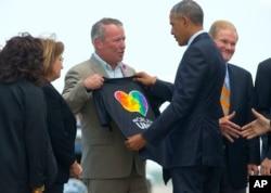 Thị trưởng Orlando Buddy Dyer đưa chiếc áo phông cho Tổng thống Obama xem khi Tổng thống đặt chân xuống sân bay Orlando hôm 16/6.