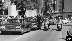 FILE - In this Nov. 22, 1963, photo, President John F. Kennedy's hand, visible through the foreground convertible's windshield, reaches toward his head within seconds of the firing of the fatal shot as first lady Jacqueline Kennedy holds his forearm, with the motorcade proceeding along Elm Street past the Texas School Book Depository in Dallas.