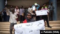 Susana Abdalla Hassan, mfanyakazi wa Benki ya Khartoum, akishikilia bango lenye kuunga mkono mapinduzi wakati wakifanya mgomo nje ya soko la bidhaa la Al-Waha mall, Khartoum, Sudan, Mei 28, 2019.