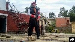 Seorang petugas keamanan berjaga di dekat lokasi serangan bom di Ghalanai, Pakistan, 15 Februari 2017 (AP Photo/Alamgir Khan).