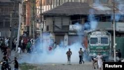 FILE - Kashmiri demonstrators throw stones towards Indian security forces during a clash following the death of Syed Ali Shah Geelani, a Kashmiri veteran separatist politician, in Srinagar, September 2, 2021.