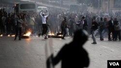 Aktivis anti-pemerintah melempar batu ke arah polisi saat bentrokan di Kairo, Mesir, Rabu (1/26).