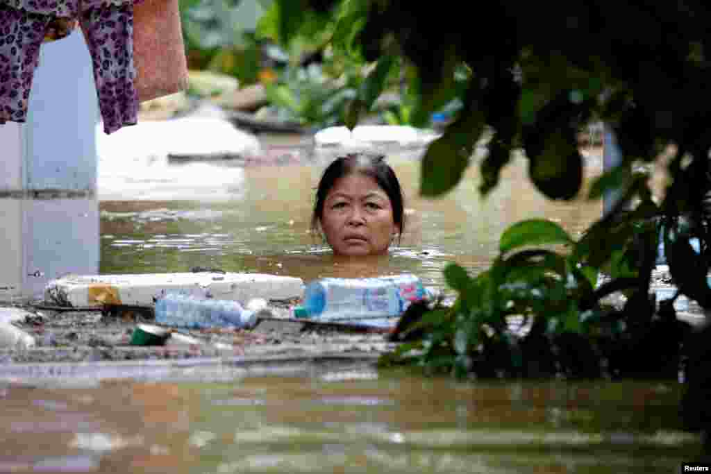 A woman wades through a submerged street at the UNESCO heritage ancient town of Hoi An after typhoon Damrey hits Vietnam.
