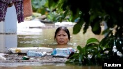 A woman wades through a submerged street at the UNESCO heritage ancient town of Hoi An after typhoon Damrey hits Vietnam, Nov. 6, 2017.