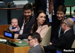 New Zealand Prime Minister Jacinda Ardern sits with her baby Neve