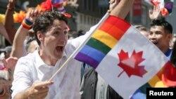 ນາຍົກການາດາ ທ່ານຈັສຕິນ ທຣູໂດ, ເສື້ອຂອງທ່ານປຽກນ້ຳຍ້ອນຖືກພວກຝຸງຄົນສີດປືນນ້ຳໃສ່, ຂະນະທີ່ເຂົ້າຮ່ວມໃນການສະໜັບສະໜຸນ ປະຊາຄົມ LGBTQ ຂອງນະຄອນ ໂຕຣອນໂຕ ຊຶ່ງພວກເຂົາເຈົ້າ ກຳລັງເດີນສວນ ສະໜາມ ໃນຄວາມພາກພູມໃຈ ທີ່ໃຫຍ່ທີ່ສຸດໃນເຂດ ອາເມຣິກາເໜືອ, ທີ່ນະຄອນໂຕຣອນໂຕ ແຂວງອອນແຕຣີໂອ ຂອງການາດາ.