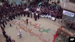 叙利亚抗议者12月30日在霍姆斯集会。地上用阿拉伯文写着:我们寻求自由与和平,我们不是小偷或逃犯。