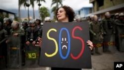 Una manifestante sostiene un cartel durante protestas frente a la fuertemente custodiada embajada cubana en Caracas.
